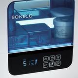 BONECO U700 - detail na displej a zásobník v provozu. Zřetelná je hodnota vlhkosti v prostoru, ikona signalizace automatického provozu a nastavení výkonu na nejvyšší úroveň. V zásobníku vody je zřejmé umístění demineralizačního filtru, který je našroubován do víka zásobníku.
